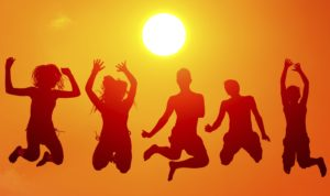 Silhouettes of teenage boys and girls jumping high in the air on